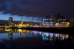 The view of the Dublin Custom House and Spire at night taken from the pedestrian footbridge.
