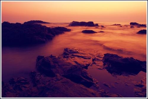 Sunset on a beautiful rocky beach between Baga and Anjuna beaches in Goa. Long exposure shot.
