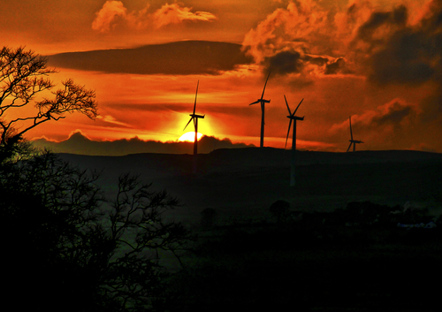 The Winter sun sets over the giant windmills at Curryfree, Derry/Londonderry, Northern Ireland.