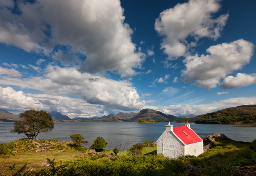 A wee house stands overlooking the loch and the Torridon Mountains in the distance.
