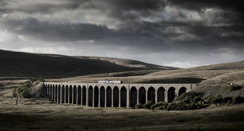 A Northern Rail Carlisle - Leeds evening service catches the evening light as it passes over the 24 arches of this spectacular remote viaduct