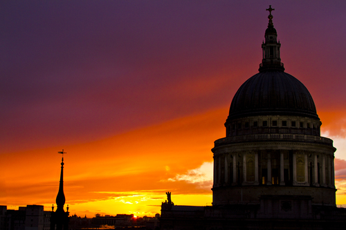 A London skyline at sunset featuring St Paul's Cathedral.