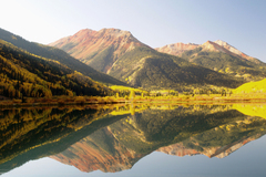 Morning light in early October sees the aspens at their peak reflected in the still waters of Crystal Lake together with Red Mountain near Ouray in the San Juan Mountains of south west Colorado.