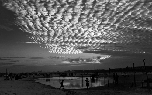 The clouds above Chennai were a sight to behold. Went all the way to the beach to be able to shoot this with some of Chennai's oldest buildings in the foreground. By the time we made it to the beach though; the clouds had receded more than we had hoped they would. So, rather than having the building as the main focus, decided to go wide and employ the clouds as the main subject.  Included one of the domes of the Madras University in the frame as well and decided to give this photo an aged effect; to get that vintage feel to the city I love.  The clouds in the frame are termed as Altocumulus Clouds.