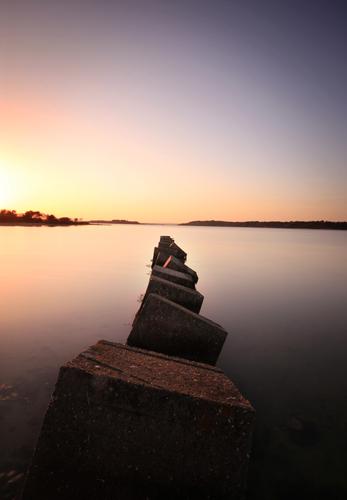 Capturing the setting Sun, giving a nice golden colour of the concrete blocks down along the shore on Blamble Bush Bay, Dorset giving that nice peaceful feeling