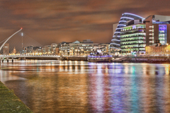 Samuel Beckett bridge, IFSC,  and the Convention centre at night reflecting on The Liffey river.