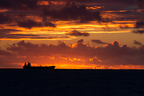 Silhouette of a fright ship and a summer sunset