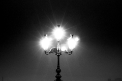 A B&W shot of a light on O'Connell Bridge with a street seller's stall beneath it.