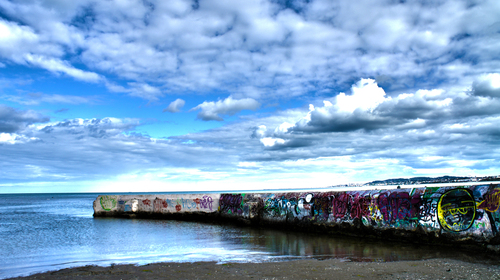 "Some colourful graffiti against a dark Irish sky, along the ""Crab House"" at Sandymount Beach"