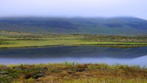 Cloudy mountain range reflected in a small lake. Shot along the Kungsleden hiking trail in Norrland, Sweden