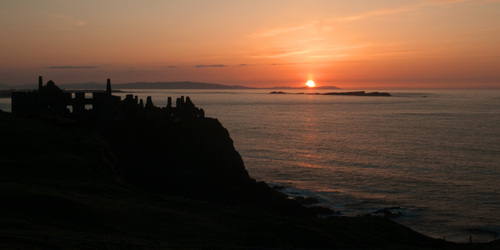 The Sun setting over Dunluce Castle on the Causeway Coast of Northern Ireland