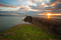 A beautiful summer sunset taken along the Great South Wall near Poolbeg, Dublin. The iconic Poolbeg power station towers are seen the background.