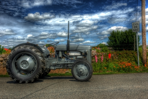 An old grey vintage tractor in HDR
