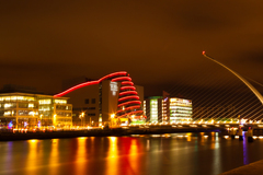 Night shot of Dublin Quay with new convention center and harp bridge.