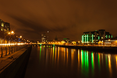 Night shot of Dublin overlooking IFSC and Custom House buildings in the site. Beautiful reflection of lights in the water