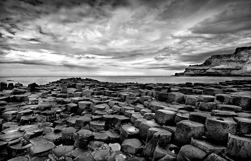 The Giant's Causeway (or Irish: Clochán na bhFómharach) is an area of about 40,000 interlocking basalt columns, the result of an ancient volcanic eruption. It is located in County Antrim, on the northeast coast of Northern Ireland, about two miles (3 km) north of the town of Bushmills. It was declared a World Heritage Site by UNESCO in 1986, and a National Nature Reserve in 1987 by the Department of the Environment for Northern Ireland. In a 2005 poll of Radio Times readers, the Giant's Causeway was named as the fourth greatest natural wonder in the United Kingdom. The tops of the columns form stepping stones that lead from the cliff foot and disappear under the sea. Most of the columns are hexagonal, although there are also some with four, five, seven and eight sides. The tallest are about 12 metres (36 ft) high, and the solidified lava in the cliffs is 28 metres thick in places.