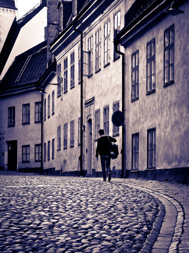Man walking home though cobbled streets in the old town of Stockholm