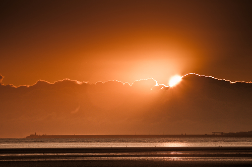Early morning sun peeks out from behind the clouds over Dun Laoghaire and Sandymount Strand