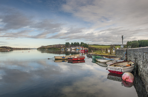 Rowing boats moored at Whiterock Bay on calm water.