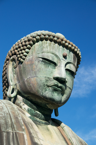 The Giant Buddha of Kamakura sits serenely against a dark blue sky