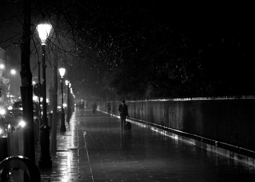 Rain falls on the passers by on a wet night in Dublin, along the railings of St Stephen's Green.
