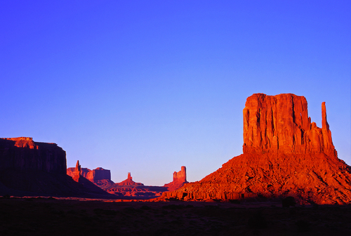 The sandstone butte known as Left Mitten turns a shade of blood orange in the evening sunlight at Monument Valley Tribal Park on the Arizona & Utah border.