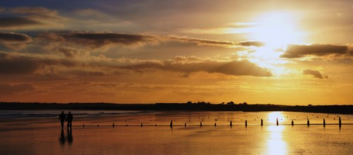 A couple take a stroll along the beach while the sun sets behind them.