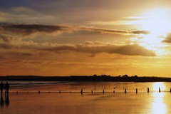 A couple take a stroll along the beach while the sun sets behind them.  Youghal Strand, County Cork, Ireland.