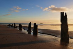 Timber beams lodged in the sand on Youghal Strand.  Youghal, Co. Cork, Ireland.