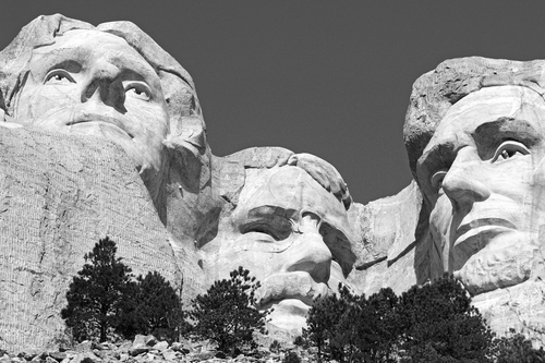 Black & white treatment of three of the stone carved presidents at the Mount Rushmore National Memorial ( Jefferson, Roosevelt and Lincoln ) in South Dakota.