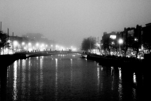 The Hapenny Bridge over the River Liffey silhouetted in the fog.