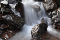 The flow of water as it cascades down a slope over the rocks.