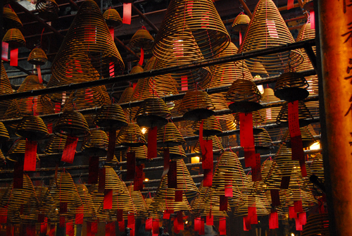 Incense coils hang from the ceiling of a Man Mo temple.