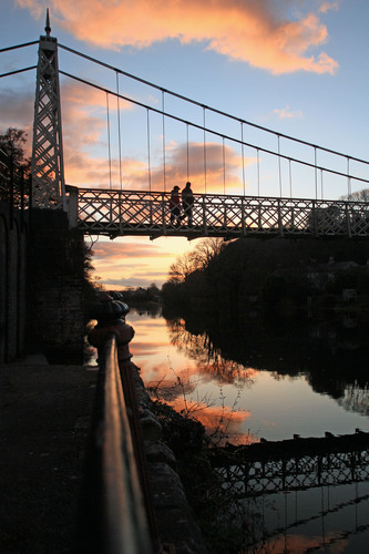 "a couple cross the ""shakey bridge""on a fine spring evening"