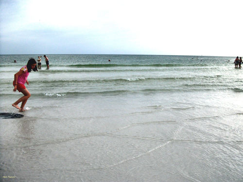 A young girl and some others play along the beach