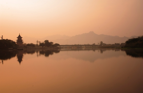 Early morning light on the Mae Klong river reveals temples and distant mountains at Kanchanaburi, western Thailand