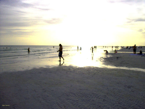 People enjoy walking along the beach with the coming sunset on the gulf coast of Florida