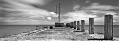 The outer harbour wall and marker of Annalong harbour.  The harbour sits in the shadow of the famous Mourne Mountains in the heart of County Down, Northern Ireland.