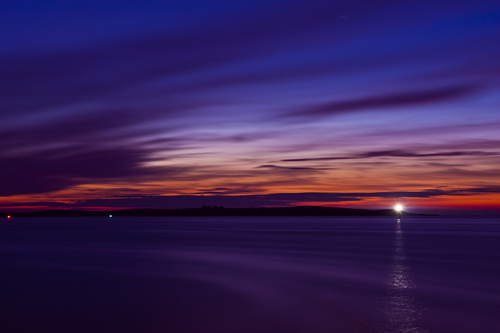 The Copeland Islands as seen from Groomsport, in County Down, Northern Ireland at night.  Inlcuded in the image are marker buoy lights and the reflection of the Copelands lighthouse.
