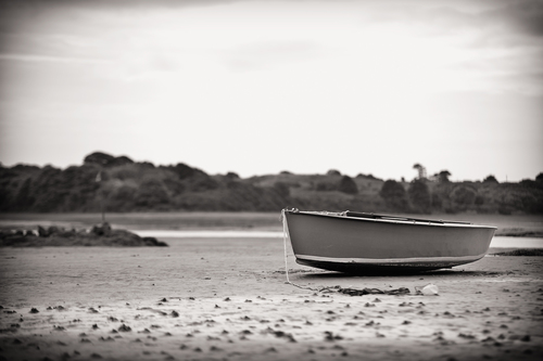 A solitary small boat beached at low tide at Dundrum, Co Down, Northern Ireland.