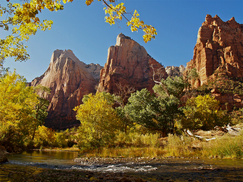 An early evening autumnal view of the Virgin River as it flows through the main valley of Zion National Park in south western Utah in beneath the towering rock faces of the Court of The Patriarchs.