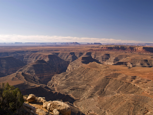 View looking over the 'goose-necks' of the San Juan River as it meanders across the Colorado Plateau in south east Utah - Monument Valley can be seen in the distance.