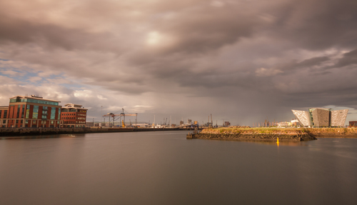 Heavy rain clouds unleash their cargo beyond the Titanic signature building, Titanic Quarter, Belfast, Northern Ireland.
