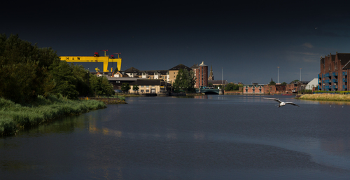 The Iconic Harland and Wolff cranes bask in a ray of sun through storm clouds, overlooking the river Lagan in Belfast.