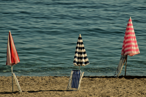 Three umbrellas on the beach with folded chairs