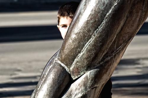 Boy hiding behind a metal statue