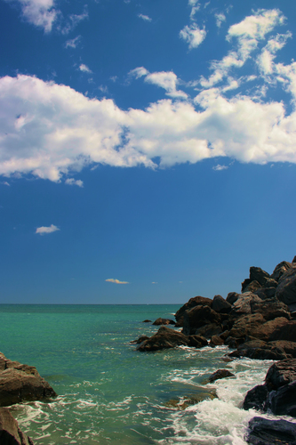 A fantastic turquoise sea, blue sky, white cloud and almost black rocks