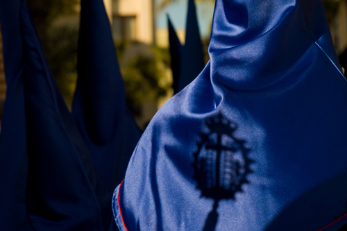 A penitente at an Easter procession has a shadow on his hood