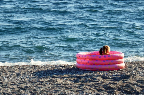 Little girl sitting in a paddling pool at the sea