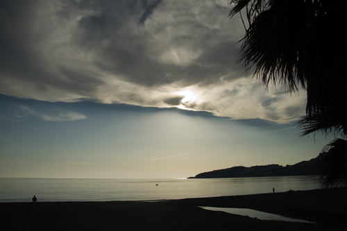 And airy cloud covering the sun and some of an empty beach and sea
